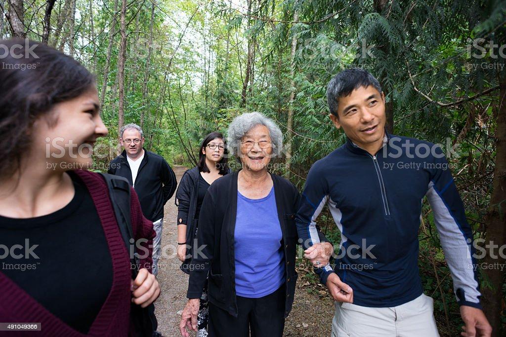 Active Mujer asiática mayor caminando en los bosques Trail con la familia - foto de stock