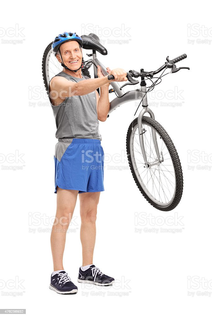 Active senior biker carrying his bicycle stock photo