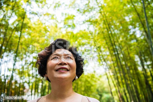 Portrait of a smiling senior Chinese woman pausing to enjoy the natural beauty of a Shanghai bamboo grove.