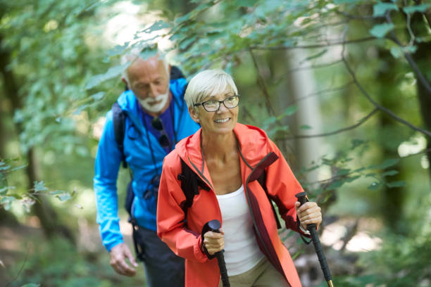 Active senior couple backpackers Active senior couple having a great time during outdoors hiking adventure. nordic walking stock pictures, royalty-free photos & images