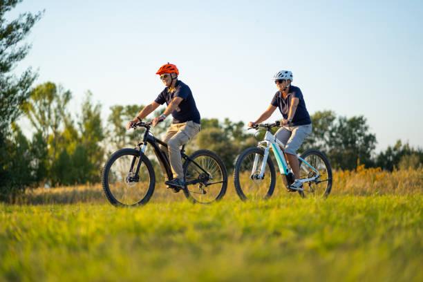 aktives seniorenpaar radelt mit mountainbikes durch die ländliche landschaft - elektrorad stock-fotos und bilder