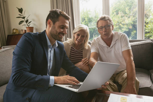 Active senior couple discussing with real estate agent over laptop in living room stock photo