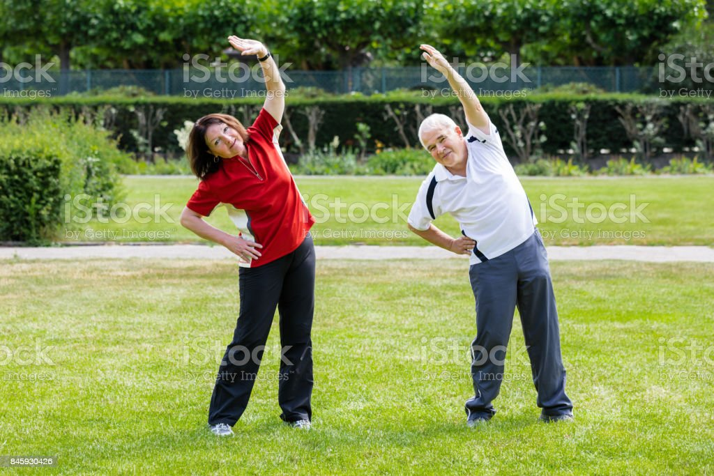 Active Senior Couple Doing Work Out In Park At Morning