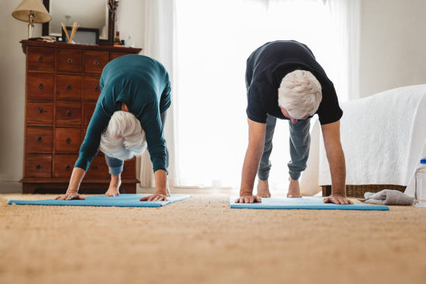 Active senior couple doing yoga together in their bedroom stock photo
