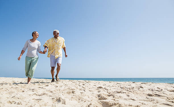 Active senior couple on the beach stock photo
