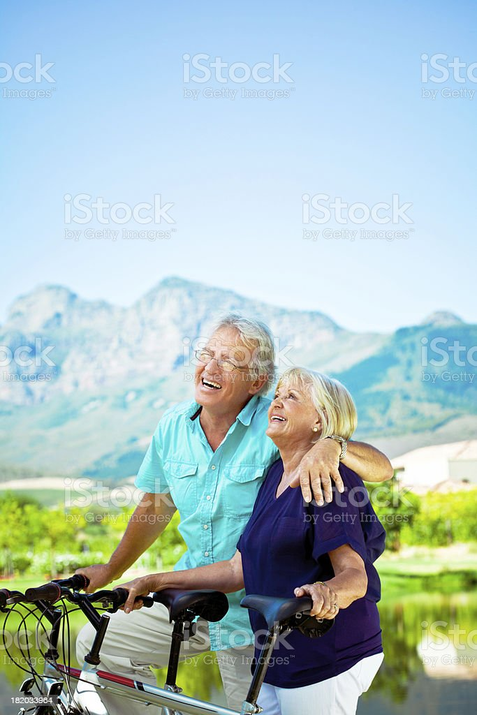 Active senior couple Outdoor portrait of happy senior couple posing with bicycles with beautiful mountains view in the background. 60-64 Years Stock Photo
