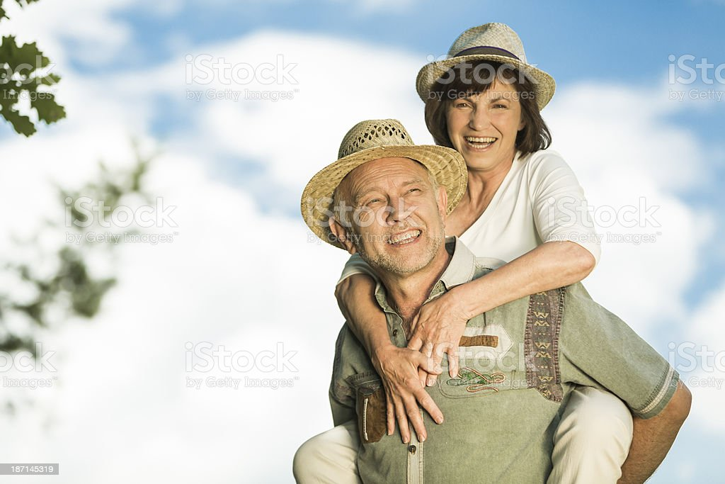 Active senior couple piggyback ride royalty-free stock photo