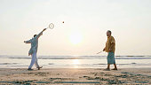 Senior couple playing tai chi ballon ball at the beach. Active leisure of aged family outdoor.