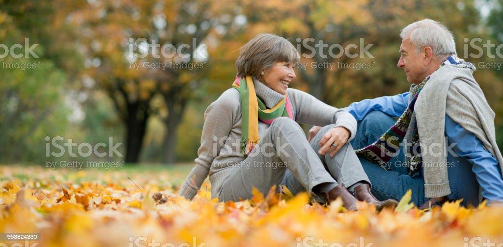 Aktive senior paar sitzt am bunten Herbstlaub im park – Foto