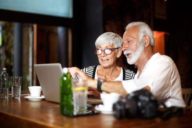 aktive senioren paar mit einem laptop zusammen in einer bar - senior bilder wasser stock-fotos und bilder