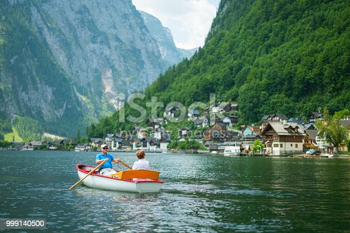 70 years old couple enjoying trip in row boat on lake between mountains in austria