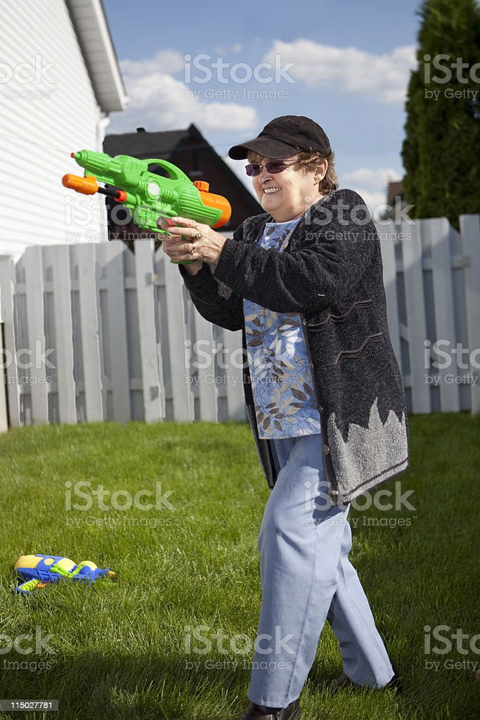 Active Senior in a Water Gun Fight stock photo