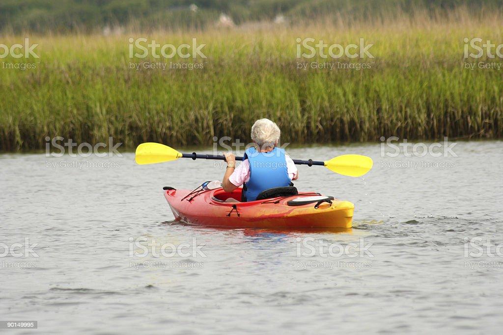 Active senior lady kayaking on the intracoastal stock photo