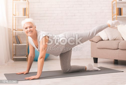 Morning work-out. Active senior lady straightening leg up, exercising at home