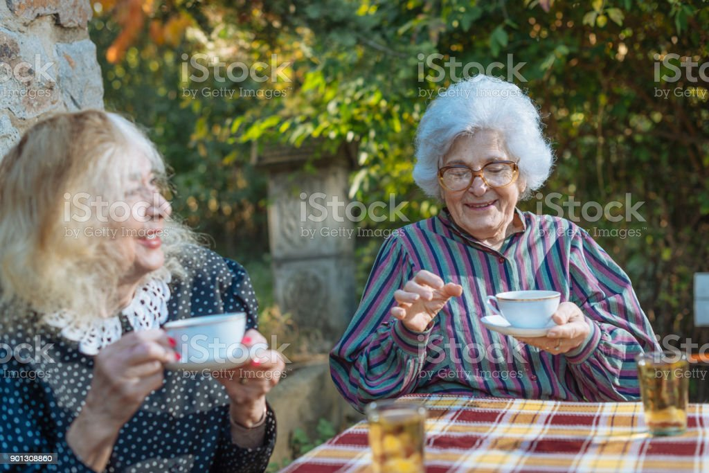 Two senior women enjoying spending time together, drinking coffee and...