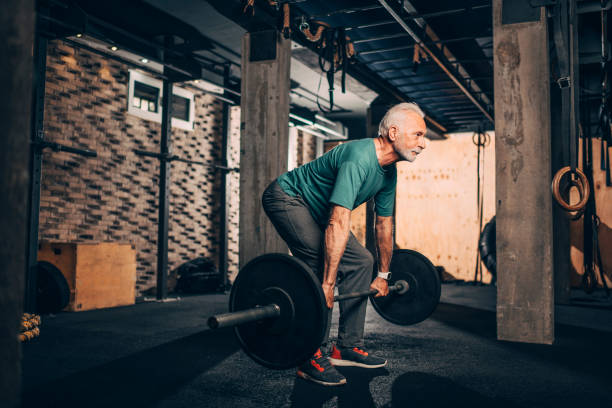 Aktives Seniorenmännchen, das eine Deadlift-Übung in einem Crossfit-Fitnessstudio macht – Foto