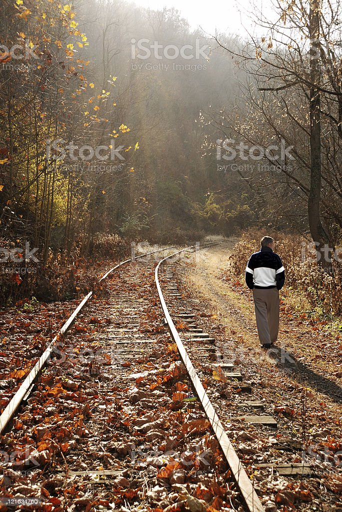 Active senior male enjoying casual walk along railroad tracks. royalty-free stock photo