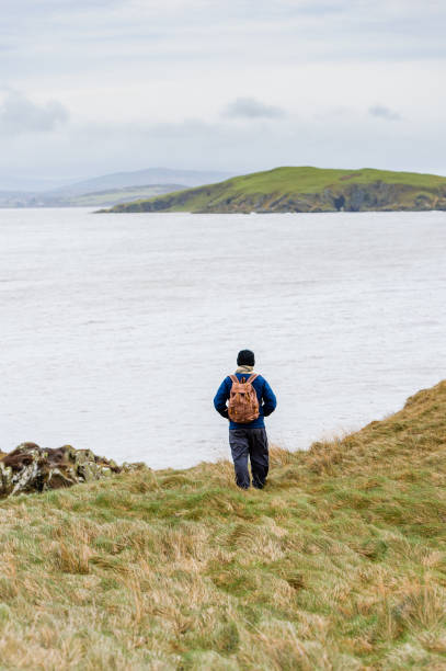 Active senior man alone on cliffs in Dumfries and Galloway looking out at the sea An active senior man dressed for winter wearing a backpack on cliffs above the sea in Dumfries and Galloway, south west Scotland. The image was captured on an overcast spring morning. johnfscott stock pictures, royalty-free photos & images