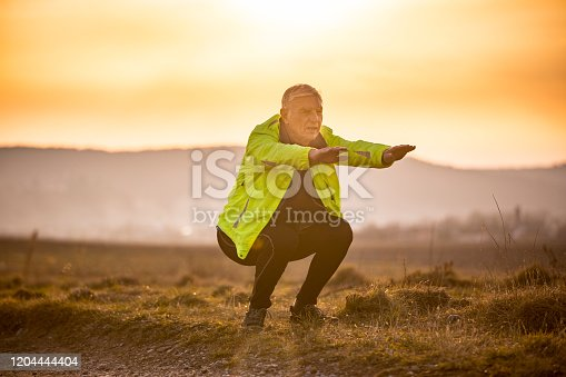 Active Senior Man Doing Squats on a Meadow During Sunset.
