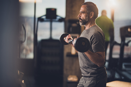 istock Active senior man having strength exercise with barbell in a gym. 909416522