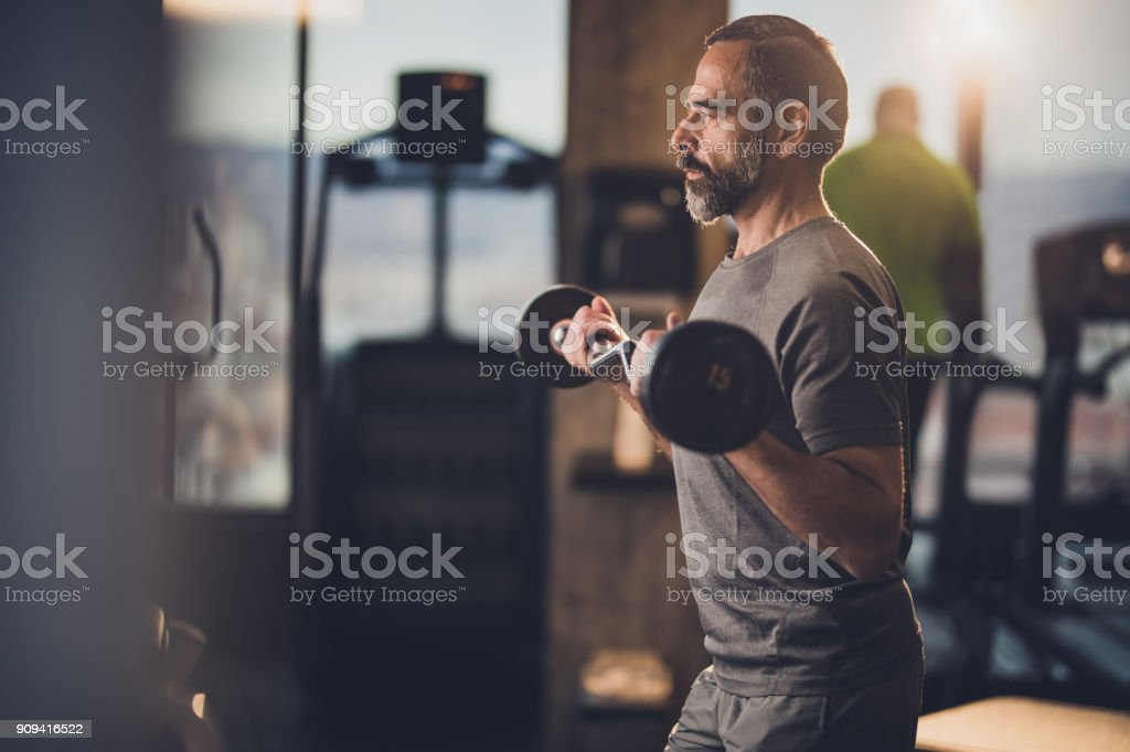 Active senior man having strength exercise with barbell in a gym. stock photo