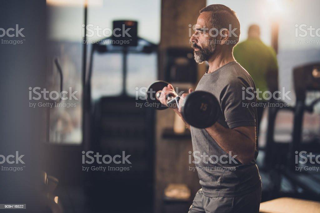 Homme senior actif ayant une résistance exercice avec haltères dans un gymnase. - Photo
