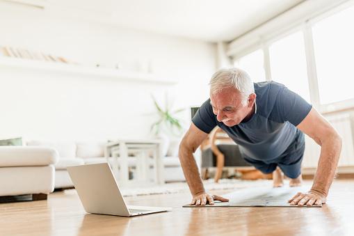 Senior man exercising at home using an online trainer service. Belgrade, Serbia