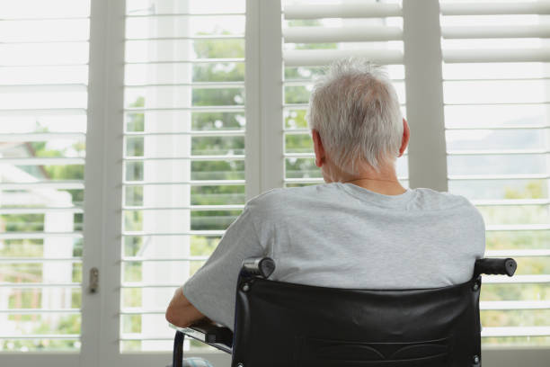 Active senior man in wheelchair looking through window at home stock photo