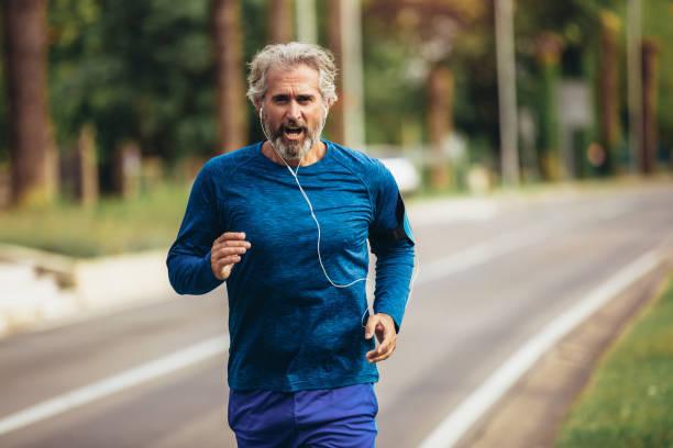 Active senior man jogging on a sunny day stock photo