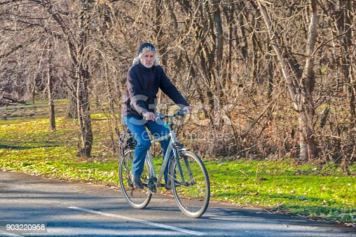 1029243348 istock photo Active senior man outdoors riding his bike. Nature. 903220958