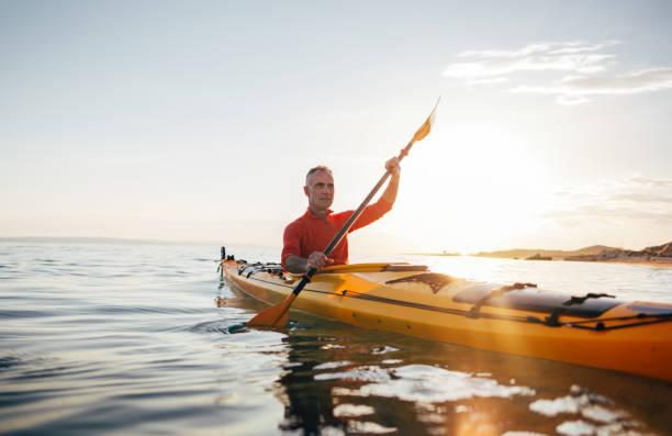 Active senior man paddling kayak stock photo
