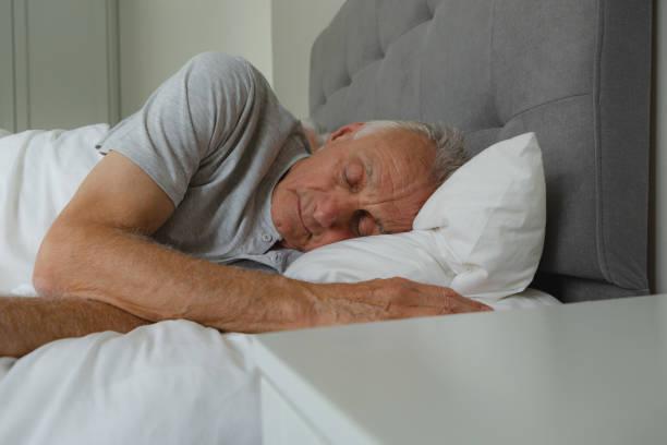 Active senior man sleeping in bed in bedroom stock photo