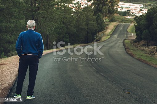 Active senior man standing on lonely road between mountains. Older man of back standing on lonely highway