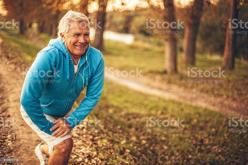 Active senior man stretching stock photo
