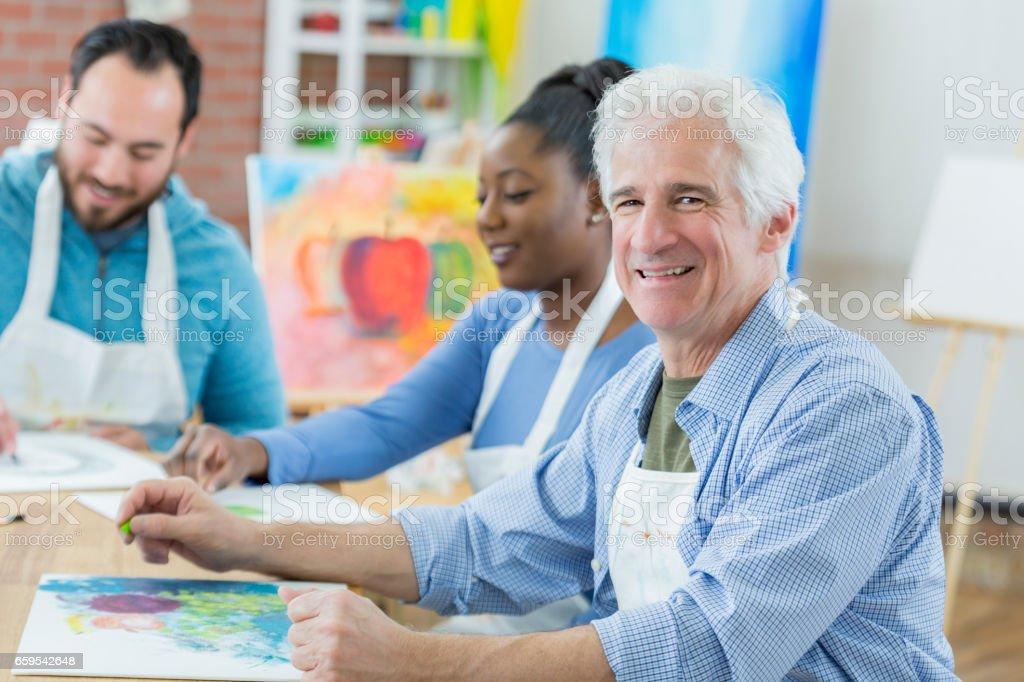 Active senior man takes art class stock photo