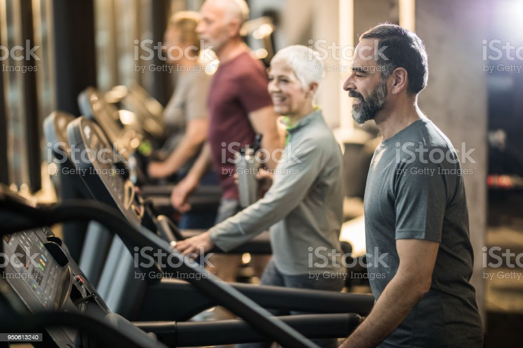 Active senior man walking on treadmill in a gym full of people. stock photo