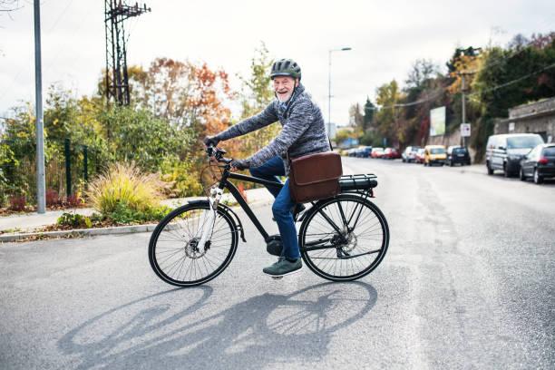 aktive ältere mann mit elektrobike radfahren im freien in der stadt. - elektrorad stock-fotos und bilder