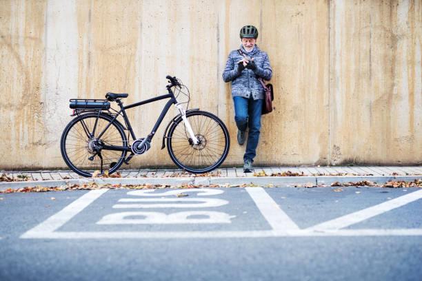 aktiven senior mann mit elektrobike stehen draußen in der stadt, mit smartphone. - elektrorad stock-fotos und bilder