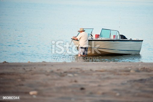 Active senior brother on a week-end fishing trip on the St. Lawrence River in Quebec Canada. We feel the tranquility of the scene. He wear fishing hat. He is 80 years old.