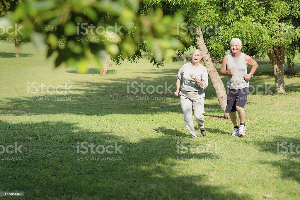 Active senior personas para trotar en el parque de la ciudad - foto de stock
