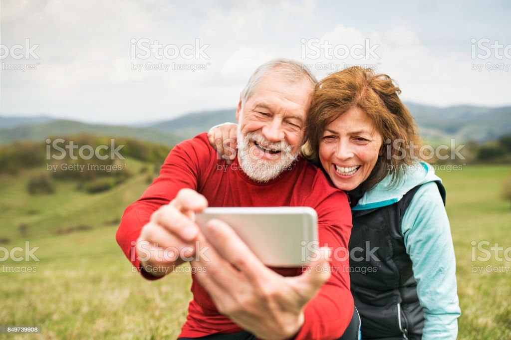 Active senior runners in nature taking photo with smart phone. stock photo