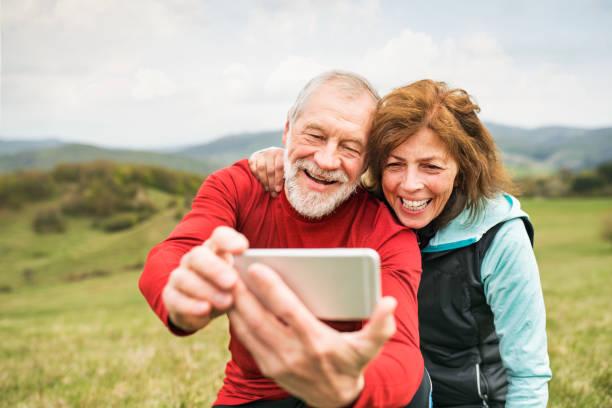 aktiva äldre löpare i naturen att ta foto med smartphone. - jogging hill bildbanksfoton och bilder