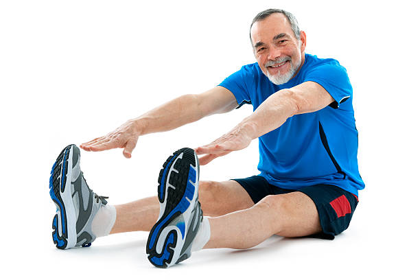 Active senior stretching and trying to reach his toes senior man  sitting and making stretching exercises  touching toes stock pictures, royalty-free photos & images