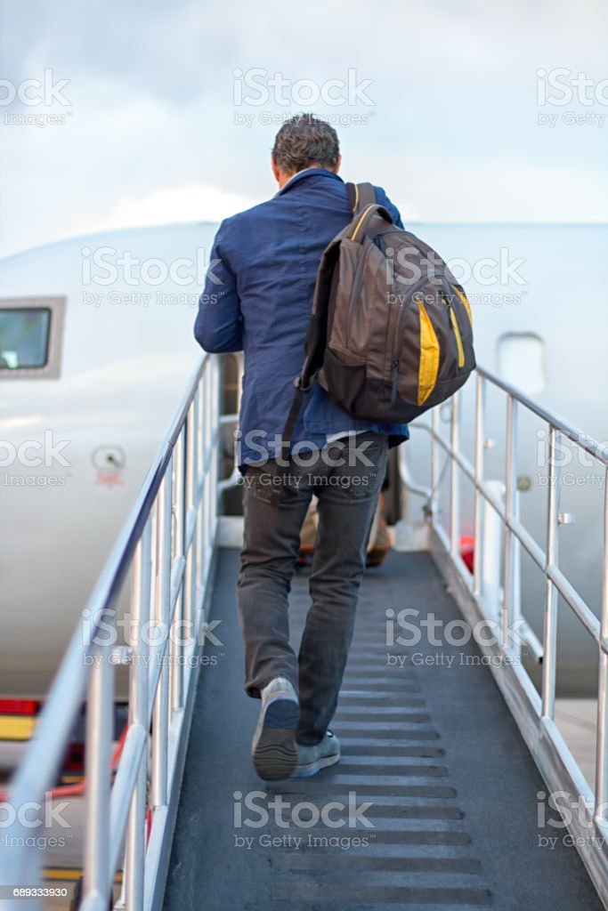 Active Senior with Backpack Boards Small Plane on Outdoor Ramp stock photo