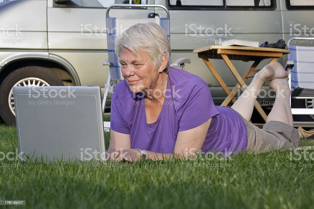 Active senior with laptop on the camping. royalty-free stock photo