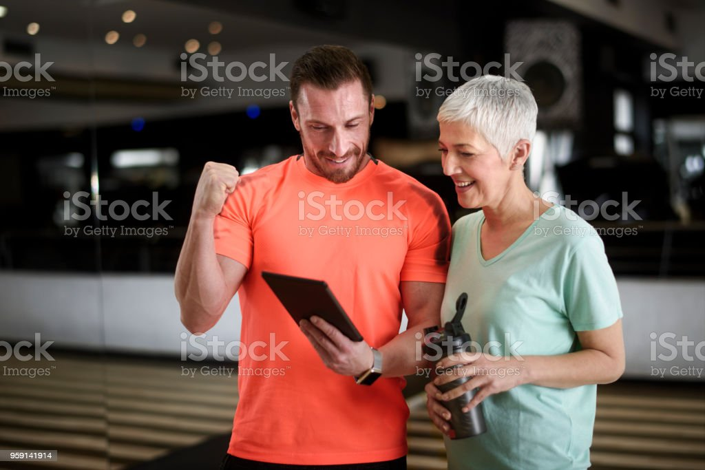 Active senior woman and fitness instructor stock photo