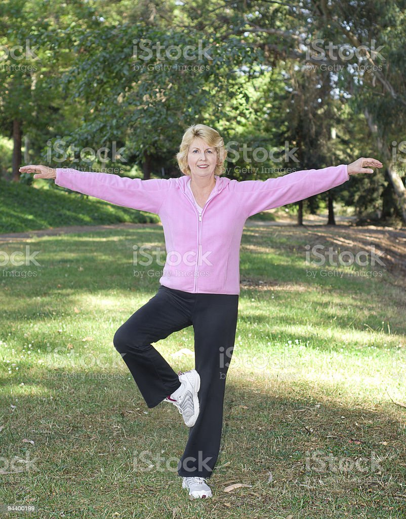 Active senior woman balancing on one leg outdoors royalty-free stock photo
