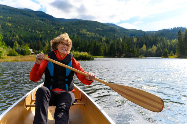 Aktive Seniorin Kanufahren im Urlaub – Foto