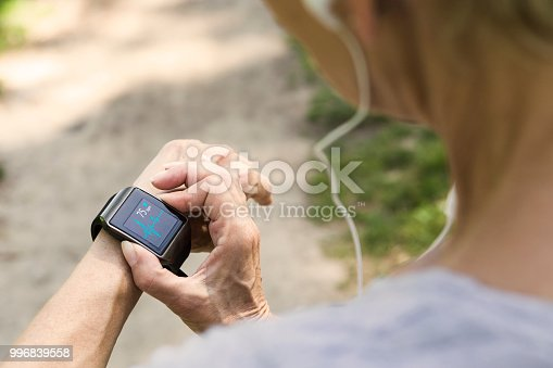 Active senior checks her heart rate on her sports watch