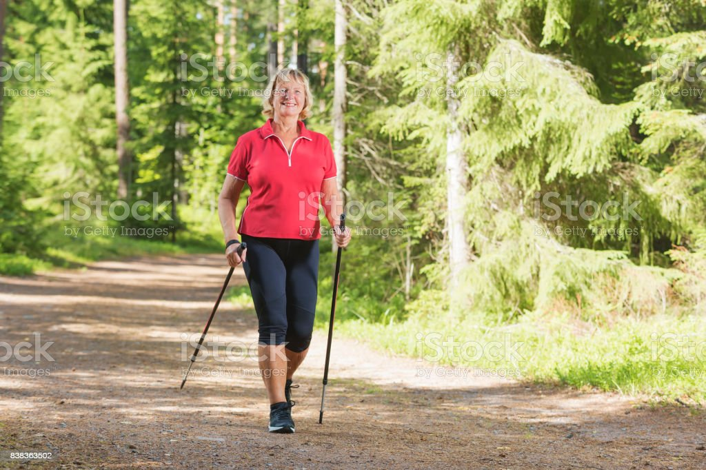 Active senior woman doing nordic walk exercise Nordic walking active senior woman working out in the forest and enjoying beautiful summer day. 60-69 Years Stock Photo